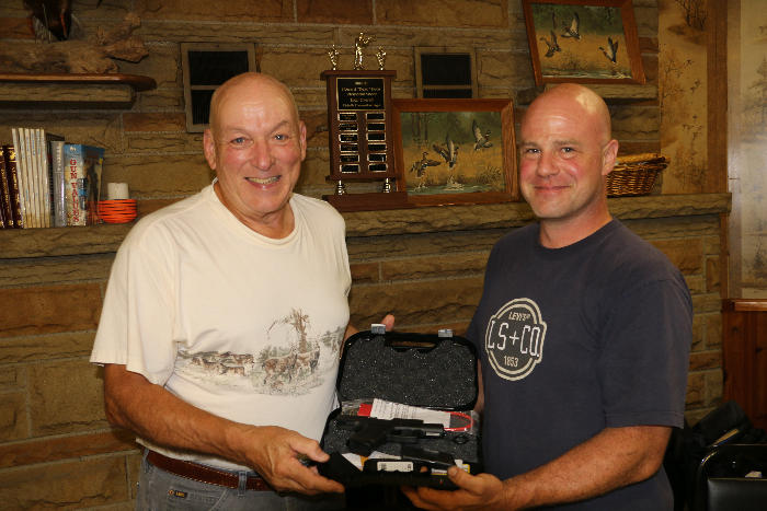 Jason Lawrence presents the gift of a 9mm Handgun to Wayne Kiser for his 25 years of leadership and service to the Fitchville Conservation League
